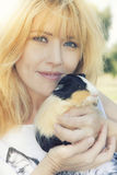 Blonde woman with Peruvian guinea pig Stock Photos