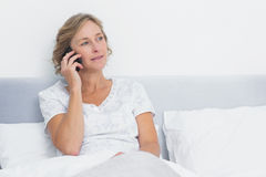 Blonde woman on the phone in bed Royalty Free Stock Photography