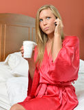 Blonde woman on phone holding coffee wearing robe Stock Photo