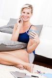 Blonde woman with phone in the living room. Royalty Free Stock Images