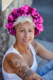 Blonde woman with a pink crown of flowers on her head and tatto. Os on her arm looking at camera stock photography