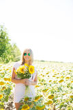 A blonde woman in a pink dress in a field with sunflowers. A woman holds a bouquet of sunflowers in her hand Royalty Free Stock Photo