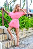 Blonde Woman In Pink Dress Posing In The Park Stock Photo