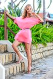 Blonde Woman In Pink Dress Posing In The Park Royalty Free Stock Image