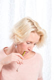 Blonde Woman in Pink Jumper Bites Pencil While Concentrating. Portrait shot of a blonde woman biting a pencil as she looks down while thinking hard. She wears royalty free stock images