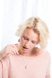 Blonde Woman in Pink Jumper Bites Pencil Whilst Concentrating. Close up portrait shot of a blonde woman biting a pencil as she looks down in concentration. She royalty free stock image