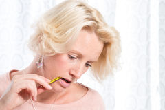 Blonde Woman in Pink Jumper Bites Pencil Whilst Thinking Hard Stock Images