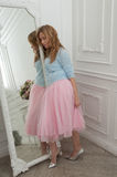 Blonde woman in pink skirt and silver shoes in classical interio Stock Images
