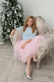 Blonde woman in pink skirt and silver shoes sit near Christmas t Stock Photos