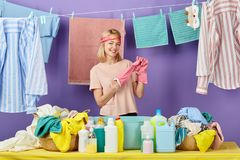 Blonde woman in pink t-shirt taking off her pink protective gloves royalty free stock photos