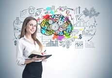 Blonde woman with a planner, brain. Smiling blonde businesswoman in a suit with a planner. A concrete wall background with a cog brain sketch on it Stock Photos