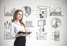 Blonde woman with a planner, infographics. Smiling blonde businesswoman in a suit with a planner. A concrete wall background with infographics on it Stock Image