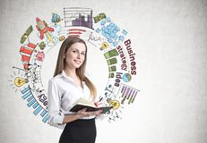 Blonde woman with a planner, strategy. Smiling blonde businesswoman in a suit with a planner. A concrete wall background with a business strategy sketch on it Stock Photos