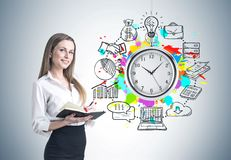 Blonde woman with a planner, time management. Smiling blonde businesswoman in a suit with a planner. A concrete wall background with time management icons on it Stock Image