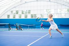 Blonde Woman Playing Tennis Action Shot stock photography