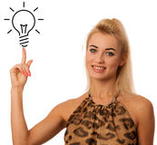 Blonde woman pointing to light bulb isolated over white backgrou Stock Images