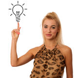 Blonde woman pointing to light bulb isolated over white backgrou Royalty Free Stock Photos
