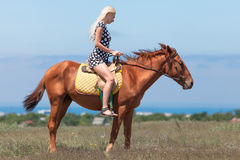Blonde woman in polka-dot dress rides on horse Royalty Free Stock Image