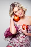 Blonde woman with pomegranates on gray Royalty Free Stock Photo