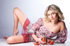 Blonde woman with pomegranates lying on gray Stock Photography