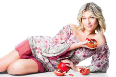 Blonde woman with pomegranates lying on isolated w Royalty Free Stock Photo