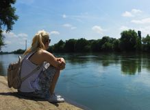 Blonde woman with pony tail, sitting by the river stock photo