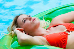 Blonde woman in pool. A blonde woman wearing red bikini in a swimming pool stock images