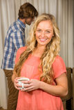 Blonde woman posing with a mug with her boyfriend behind Royalty Free Stock Photos