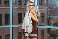 Blonde woman posing near the large window with city views Royalty Free Stock Photos