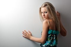 Blonde woman posing near wall Royalty Free Stock Image