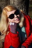 Blonde woman posing with red jacket and sunglasses Royalty Free Stock Image