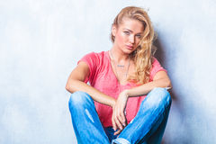 Blonde woman posing while sitting on the floor looking at the ca Royalty Free Stock Images