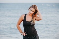Blonde woman posing in sportswear at the beach. Stock Photography