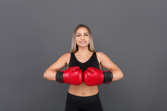 Blonde woman posing wearing boxing gloves stock photography