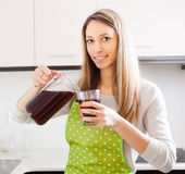 Blonde woman pouring fresh quass into glass Stock Photo