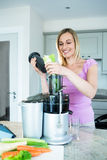 Blonde woman preparing a smoothie in the kitchen Stock Images