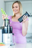 Blonde woman preparing a smoothie in the kitchen Stock Image