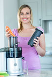 Blonde woman preparing a smoothie in the kitchen Stock Photography