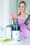 Blonde woman preparing a smoothie in the kitchen Royalty Free Stock Photography
