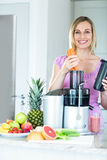 Blonde woman preparing a smoothie in the kitchen royalty free stock photos