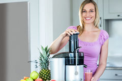 Blonde woman preparing a smoothie in the kitchen stock photo