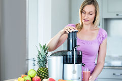 Blonde woman preparing a smoothie in the kitchen royalty free stock image