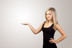 Blonde woman presenting hand. Copyspace on left Royalty Free Stock Photography