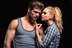 Blonde woman pulling her boyfriends chin with her finger Stock Image