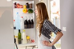 Blonde woman pulls out from the refrigerator products Royalty Free Stock Image