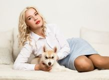 Blonde woman with puppy husky dog on a white sofa. girl playing with a dog Royalty Free Stock Image