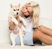 Blonde woman with puppy husky dog on a white sofa. girl playing with a dog Royalty Free Stock Photos