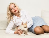 Blonde woman with puppy husky dog on a white sofa. girl playing with a dog.  Stock Images