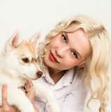 Blonde woman with puppy husky dog on a white sofa. girl playing with a dog Stock Image