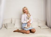 Blonde woman sitting on a sofa with puppy husky dog. girl playing with a dog Stock Photo